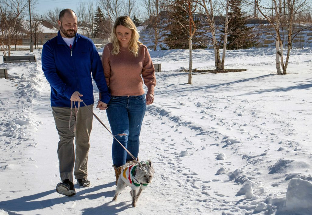 Avery and Andy Hallberg take their dog, Lola, for a walk on a sunny winter day.
