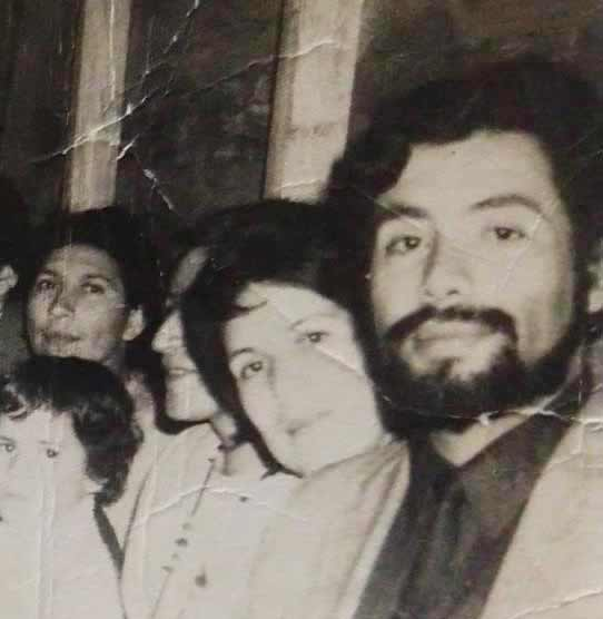 A row of people. Closest to the camera is a long-haired, bearded man in a suit and a woman with her neck resting on the man's shoulder.