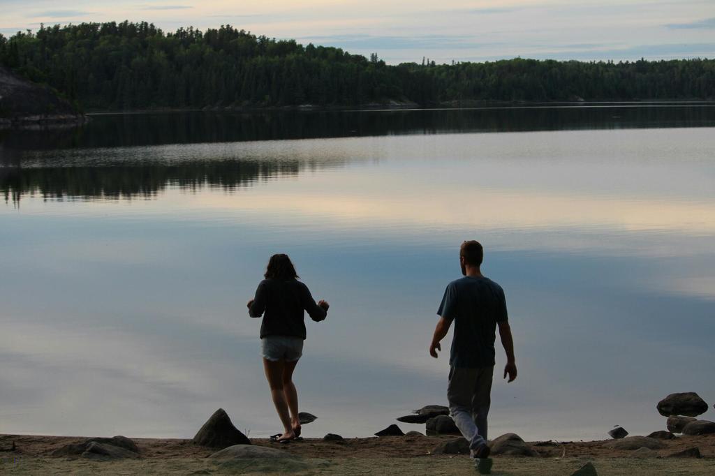 Two people walking towards a lake at dusk.