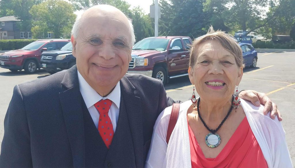 An elderly couple, dressed for church, smile at the camera in a parking lot.