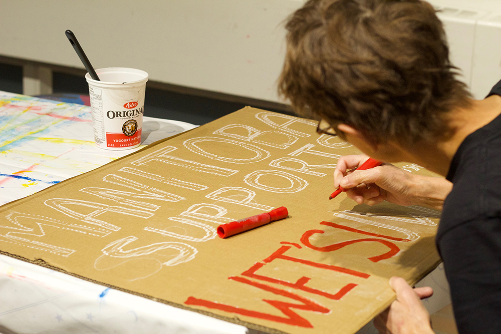 Protestor painting a sign