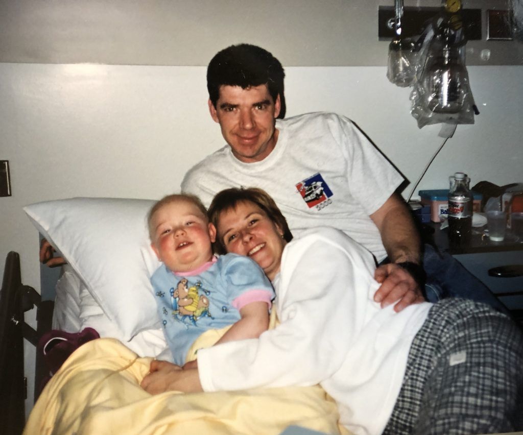 A picture of my parents and I  sitting in a hospital bed during my treatments.