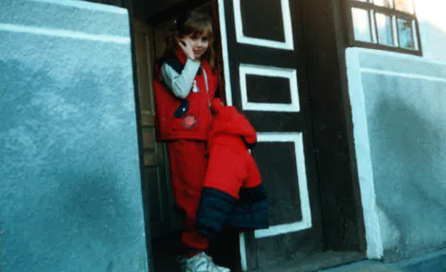 A photo of me at age seven standing in the doorway of our house in Ukraine about to meet my dad for the first time since he went away.
