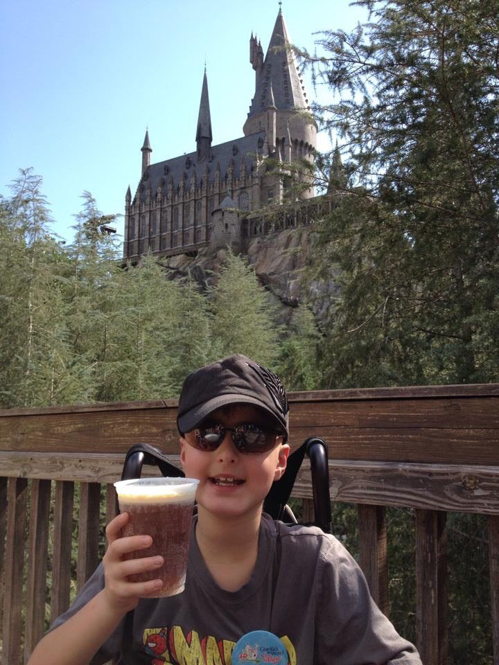 Madox in front of Hogwarts Castle at The Wizarding World of Harry Potter in Orlando. He is holding a cup of Butterbeer and is sitting in a wheelchair.