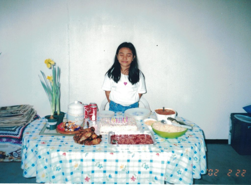 Alyssa standing in front of a dinner table with food