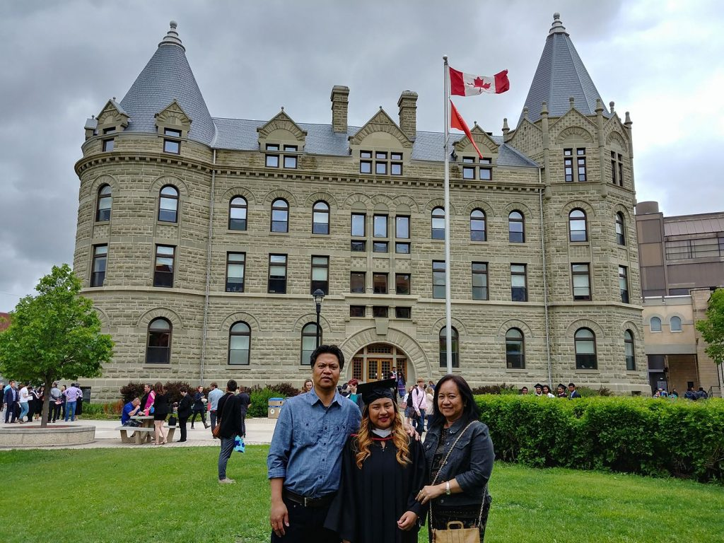Mom, dad, and I standing in front of The University of Winnipeg.