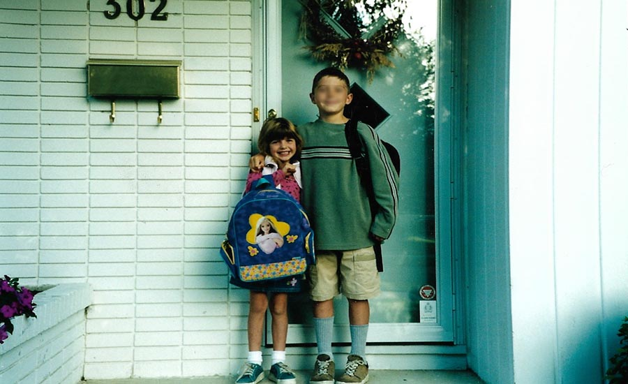 A young boy and girl standing outside a house, both wearing backpacks, posing before their first day of school.