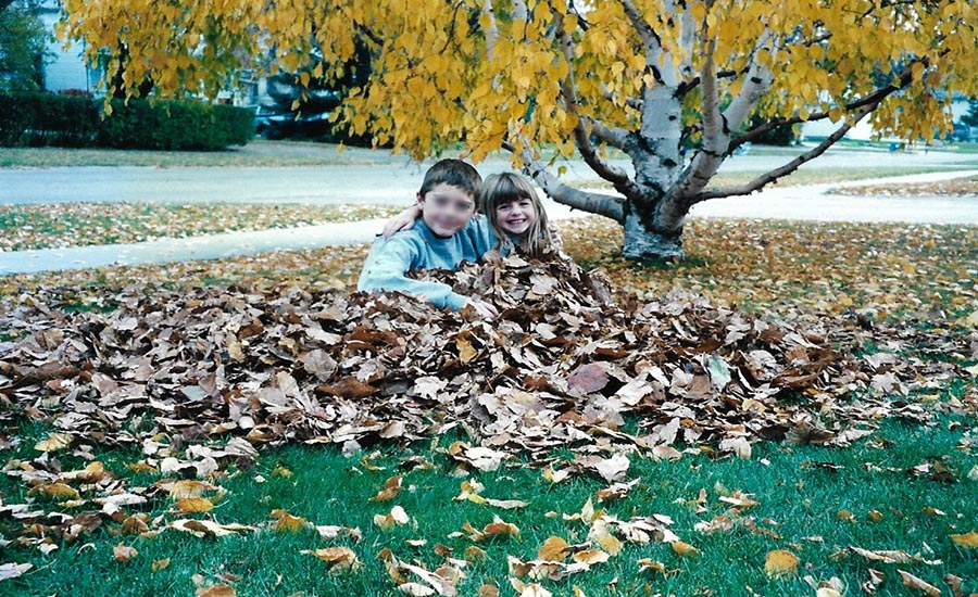 A young boy and girl sitting in a pile of leaves with their arms around each other