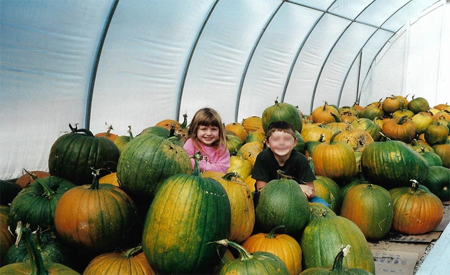 A young boy and girl sitting in a pile of pumpkins in a greenhouse