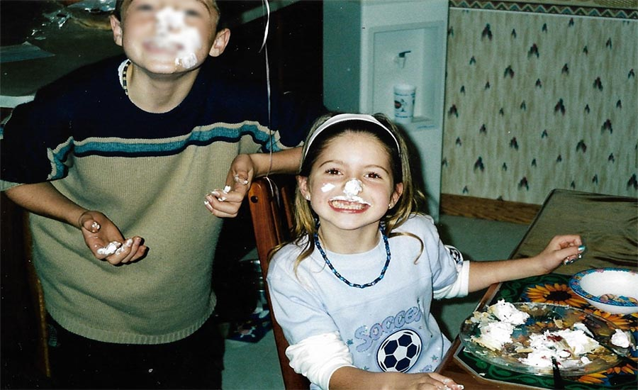 Two children with cake on their faces smiling at the camera.