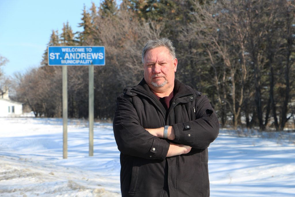 "Tom Watson stands in front of a ""Welcome to St. Andrews Municipality"" sign."